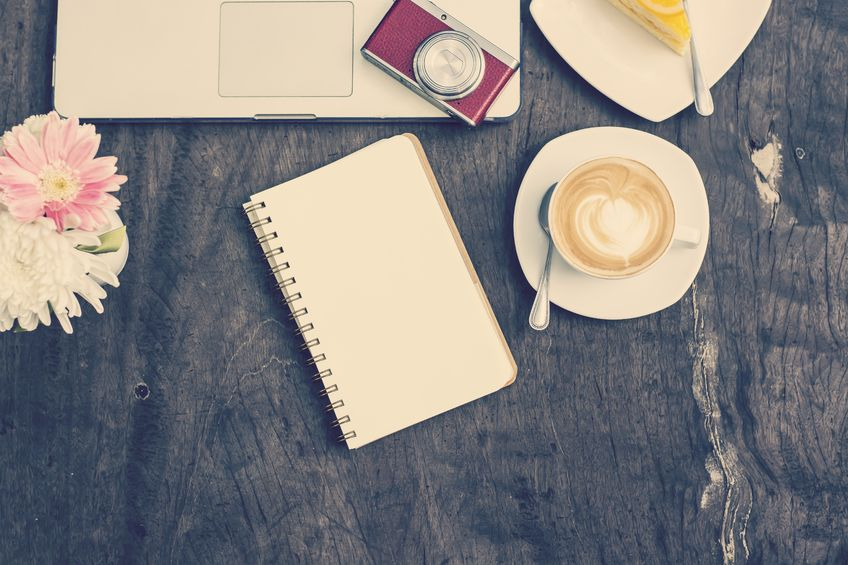 57333125 - blank notebook with laptop and pen on wood table, vintage tone