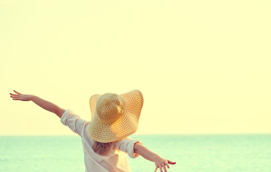 41789381 - happy beauty woman in hat is back opened his hands, relaxes and enjoys the sunset over the sea on the beach